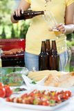 Young woman pouring beer Royalty Free Stock Photos