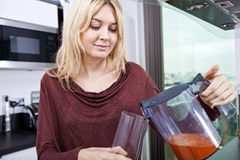 Young woman pouring carrot juice in glass at kitchen Stock Images
