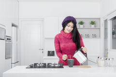 Young woman pouring coffee in the kitchen Stock Photo