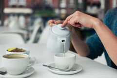 Young woman pouring a cup of tea Stock Image