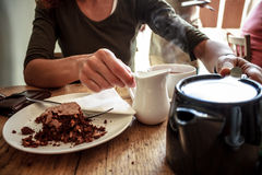 Young woman pouring cup of tea and eating cake in cafe. Young woman pouring herself a cup of tea and eating cake in cafe Royalty Free Stock Images