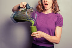 Young woman pouring a green smoothie Stock Photo