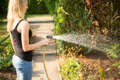 Young woman pouring her garden stock photos