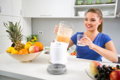Young woman pouring juice from blender in the glass Stock Photos