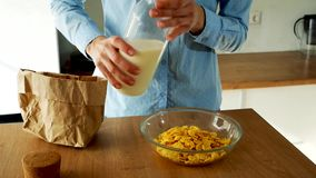 Young woman pouring milk into a bowl of cornflakes in the kitchen. Slow motion video stock video