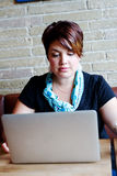 Young woman pouring over computer Royalty Free Stock Photos