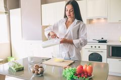 Young woman is pouring some milk into glass bowl with eggs. There are plenty of food at the table. Girl is cooking. Young woman is pouring some milk into glass royalty free stock images