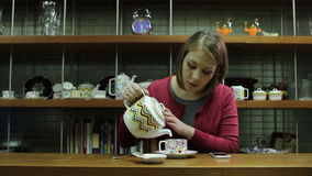 Young woman  pouring tea by dinning table stock footage