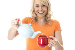 Young Woman Pouring Tea from a Teapot royalty free stock photo