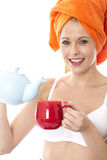 Young Woman Pouring Tea from a Teapot Stock Image