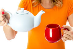 Young Woman Pouring Tea from a Teapot Holding Teapot and Mug Royalty Free Stock Photography