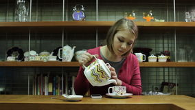 Young woman  pouring tea  and watching on cellphone stock footage
