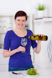 Young woman pouring white wine in a glass in her kitchen Royalty Free Stock Photos