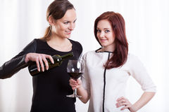 Young woman pouring wine for her friend Royalty Free Stock Photos