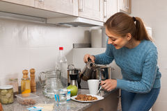 Young woman pours a cup of coffee in the kitchen Royalty Free Stock Photo