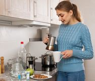 Woman pours a cup of coffee in the kitchen Stock Photography