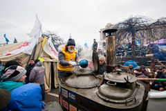 Young woman pours hot tea from a huge barrel of the street kitchen on the crowded Maidan square during anti-government protest Stock Photo