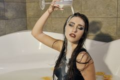 Young woman pours milk on herself. Woman with smeared makeup stock photography