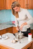 Young woman pours milk in pot. Young woman pours milk in a pot Stock Image