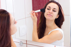 Young woman powdering in bathroom. Young attractive woman with long dark hair in white shirt powdering with silver brush in front of the mirror in her burgundy royalty free stock photography