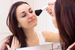 Young woman powdering in bathroom. Beautiful young woman with long dark hair in white shirt powdering with silver brush in front of the mirror in her burgundy royalty free stock photography