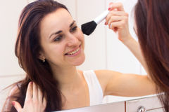 Young woman powdering in bathroom. Charming young woman with long dark hair in white shirt powdering with silver brush in front of the mirror in her burgundy stock photos