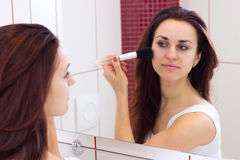 Young woman powdering in bathroom. Young elegant woman with long dark hair in white shirt powdering with silver brush in front of the mirror in her burgundy stock photography