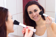 Young woman powdering in bathroom. Young happy woman with long dark hair in white shirt powdering with silver brush in front of the mirror in her burgundy stock photos