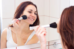 Young woman powdering in bathroom. Happy young woman with long dark hair in white shirt powdering with silver brush in front of the mirror in her burgundy royalty free stock photo