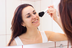 Young woman powdering in bathroom. Nice young woman with long dark hair in white shirt powdering with silver brush in front of the mirror in her burgundy royalty free stock photos
