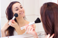 Young woman powdering in bathroom Royalty Free Stock Photos