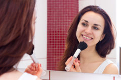 Young woman powdering in bathroom. Young optimistic woman with long dark hair in white shirt powdering with silver brush in front of the mirror in her burgundy royalty free stock photos