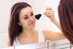 Young woman powdering in bathroom. Pleasant young woman with long dark hair in white shirt powdering with silver brush in front of the mirror in her burgundy royalty free stock photography