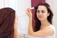 Young woman powdering in bathroom. Young pretty woman with long dark hair in white shirt powdering with silver brush in front of the mirror in her burgundy royalty free stock image