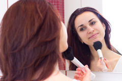 Young woman powdering in bathroom. Young smiling woman with long dark hair in white shirt powdering with silver brush in front of the mirror in her burgundy royalty free stock images