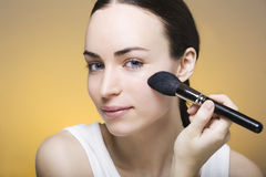 Young woman powders her skin with a makeup brush Stock Images