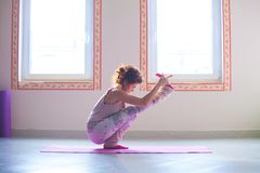 Young woman practice yoga indoor full body shot Royalty Free Stock Photos