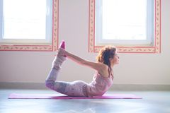 Young woman practice yoga indoor full body shot Royalty Free Stock Photography
