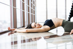 Young woman practice yoga matsyasana against windows in studio. Stock Image