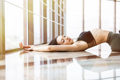 Young woman practice yoga matsyasana against windows in studio. Royalty Free Stock Photo