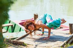 Young woman practice yoga outdoor by the lake balance pose on hands healthy lifestyle concept royalty free stock photos