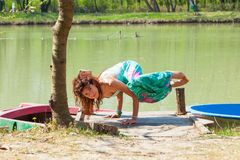 Young woman practice yoga outdoor by the lake balance pose on hands healthy lifestyle concept royalty free stock photo