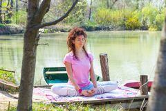 Young woman practice yoga outdoor by the lake healthy lifestyle concept. D royalty free stock photo