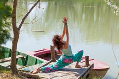 Young woman practice yoga outdoor by the lake healthy lifestyle concept sumer day royalty free stock photos