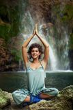 Young woman practice yoga outdoor on the rocks by the waterfall Royalty Free Stock Photos