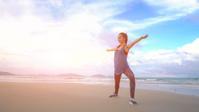 Young woman practices yoga on a beach at sunrise in front of sea. Morning gymnastic. Healthy lifestyle. Rise hands Stock Image