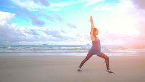 Young woman practices yoga on a beach at sunrise in front of sea. Morning gymnastic. Healthy lifestyle. Rise hands Royalty Free Stock Images