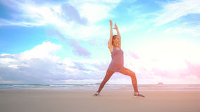 Young woman practices yoga on a beach at sunrise in front of sea. Morning gymnastic. Healthy lifestyle. Rise hands Royalty Free Stock Photo