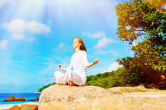 Young woman practices yoga on the beach Royalty Free Stock Images
