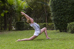 Young woman practices yoga in garden, Thailand Stock Photography